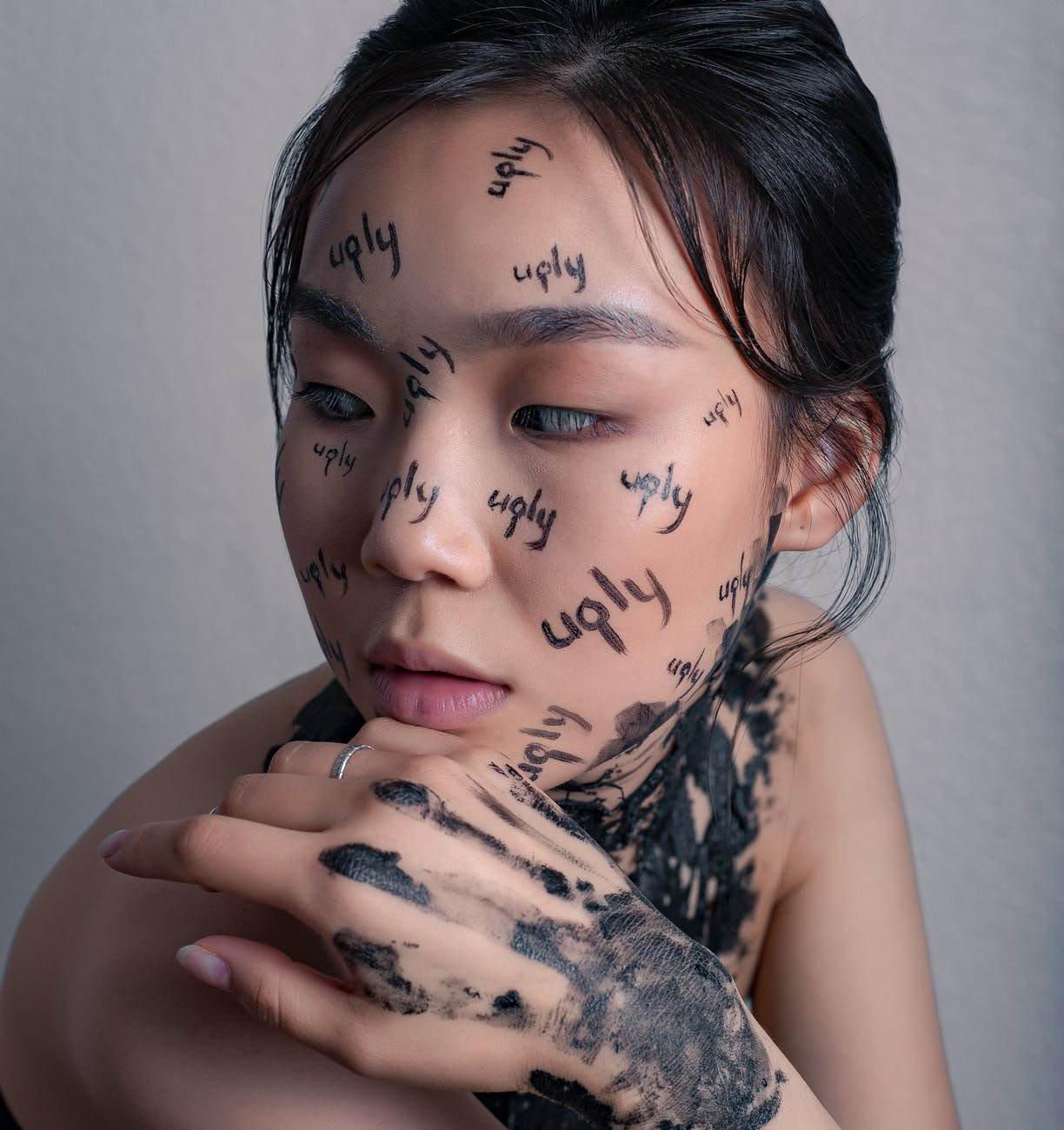 crop asian woman with words ugly written on face