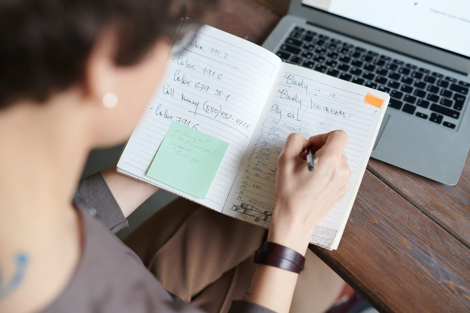 photo of person writing on notebook