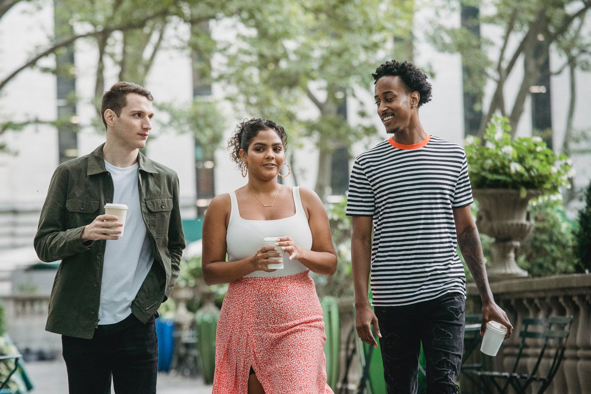 positive young diverse millennials walking in park and drinking coffee after studies